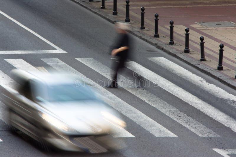 Gångare och en körande bil på zebramarkering arkivfoto