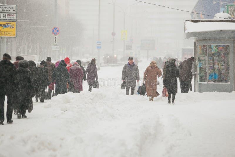 Gångare som fortskrider den snöig trottoaren i tung häftig snöstorm royaltyfri bild
