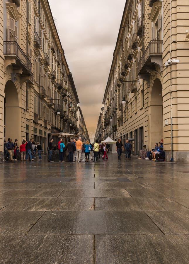 Gångare som promenerar en våt gata i Turin royaltyfria foton