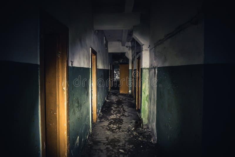Gångbana i kuslig övergiven byggnad, mörk läskig korridor med många dörrar, fasabakgrundsbegrepp arkivfoton