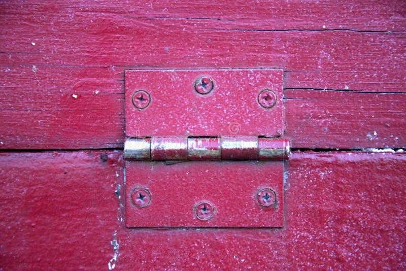 Gångjärn på rött trä arkivbild