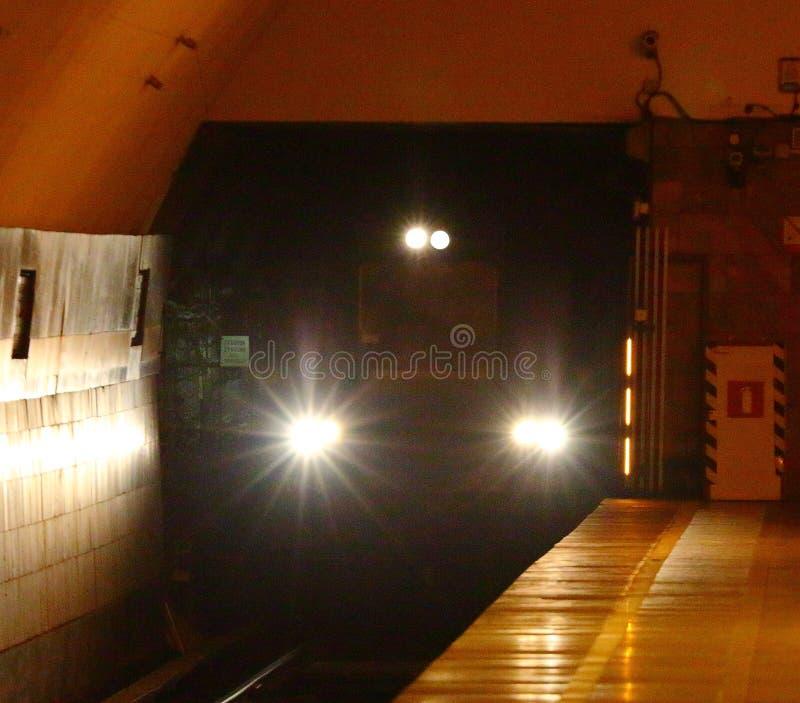 Gångtunneldrev som dyker upp från en tunnel av tunnelbanastationen arkivbilder