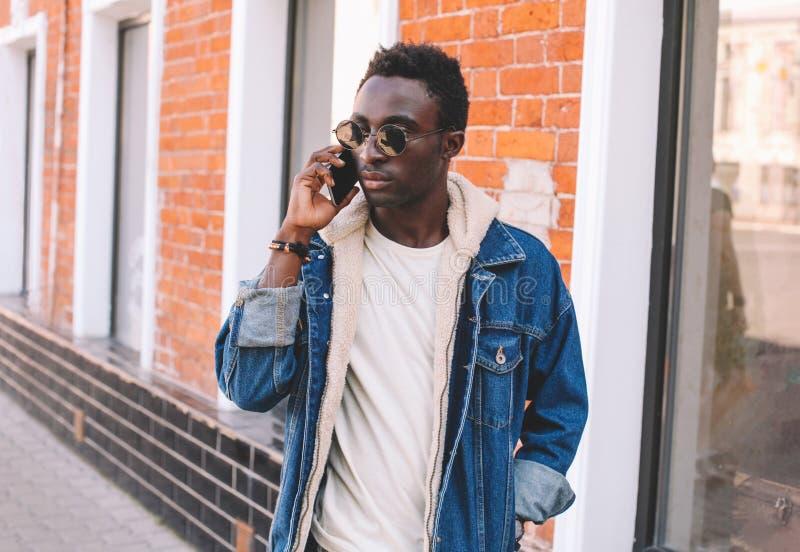 Går den afrikanska mannen för mode som talar på smartphonen, på stadsgatan royaltyfria bilder