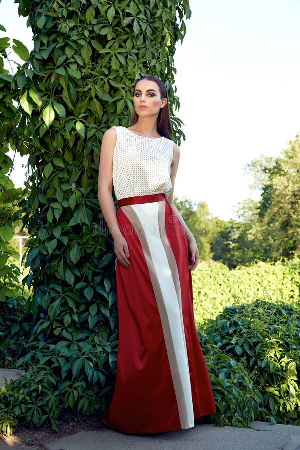 Går den bärande klänningen för den härliga sexiga kvinnan parkerar solskenmakeup fotografering för bildbyråer
