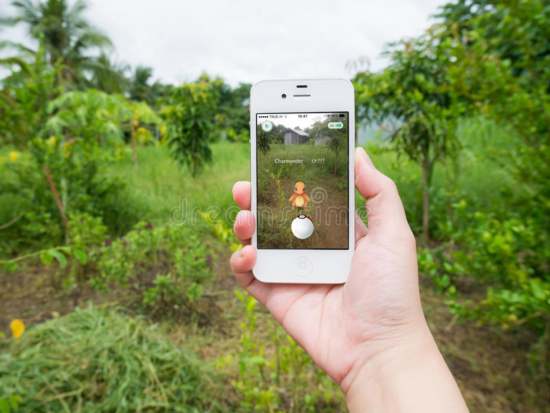 Går den hållande mobiltelefonen för handen som spelar Pokemon royaltyfri fotografi