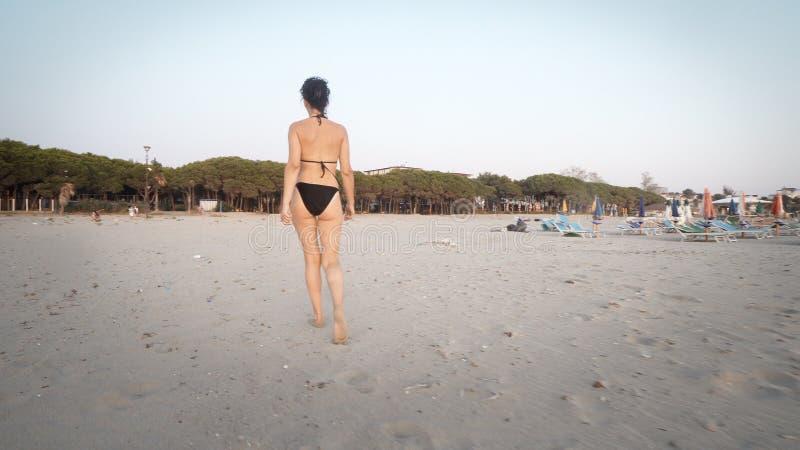 Går den kvinnliga modellen för mode i bikini på tom strandsand på soluppgång arkivbild
