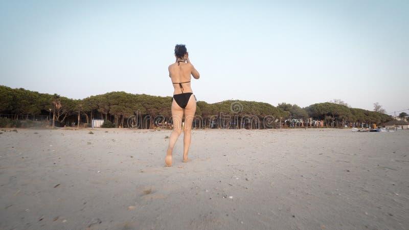 Går den kvinnliga modellen för mode i bikini på den tomma stranden arkivfoton