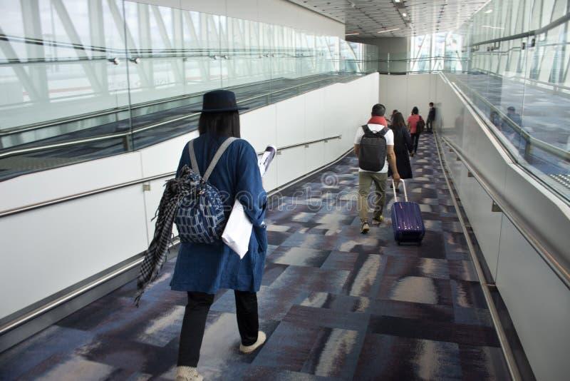 Går den thai kvinnan för handelsresande som går i terminal, till bussstationen på Hong Kong International Airport arkivfoto