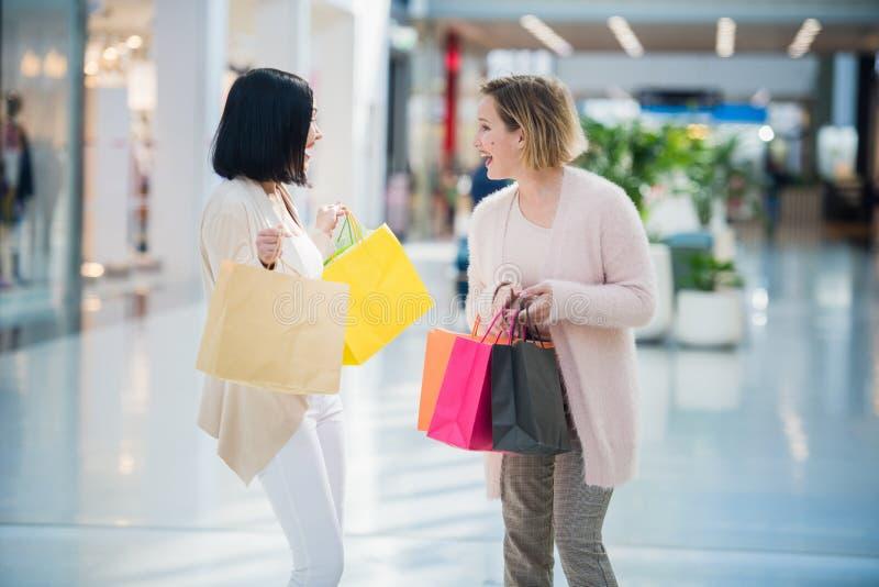 Går gullig flicka två i gallerian med gåvapåsar Lyckligt och le, når att ha shoppat med många köp arkivfoto