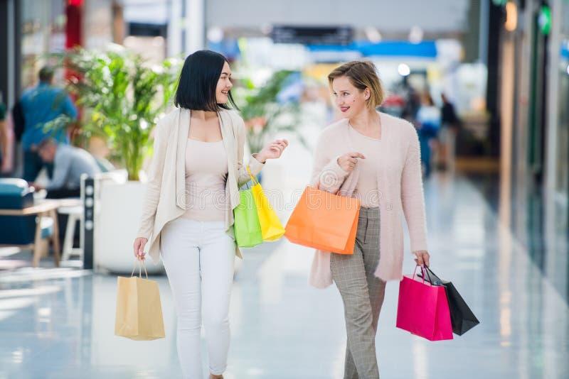 Går gullig flicka två i gallerian med gåvapåsar Lyckligt och le, når att ha shoppat med många köp royaltyfri bild