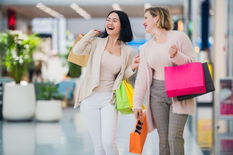 Går gullig flicka två i gallerian med gåvapåsar Lyckligt och le, når att ha shoppat med många köp royaltyfria bilder