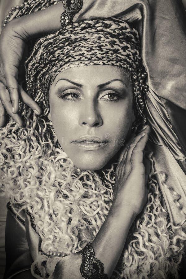 Gåtfull flätad trådhårstil och skönhet Guld- och silverstående av en härlig kvinna royaltyfri fotografi