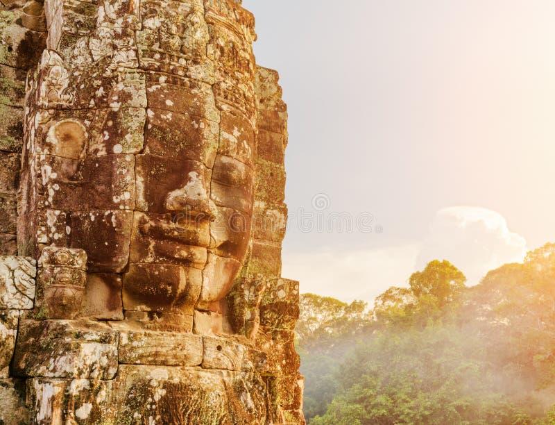 Gåtfull jätte- stenframsida av den Bayon templet i aftonsol royaltyfri foto
