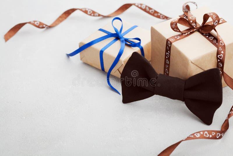 Gåva eller gåvaask med bandet och bowtie på det gråa skrivbordet för lycklig faderdag, kopieringsutrymme för din text eller desig royaltyfria foton