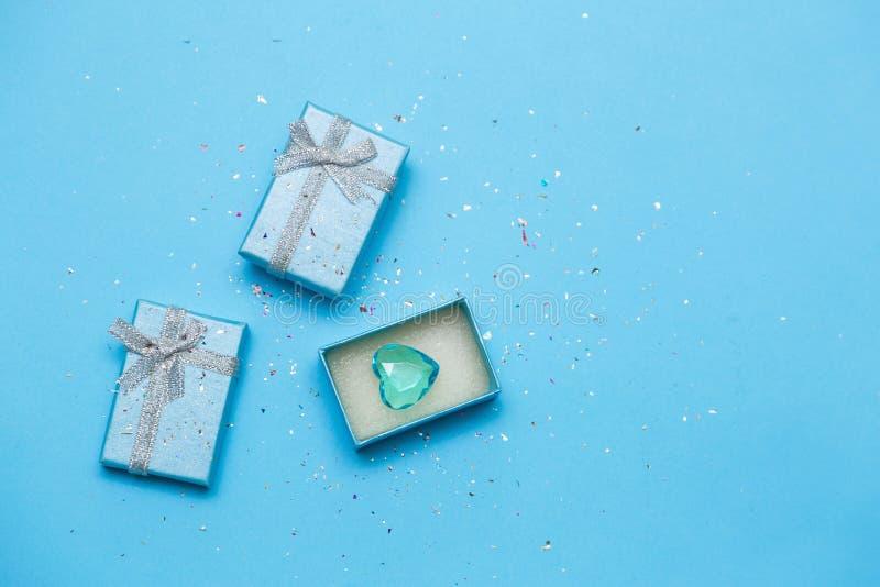 Gåva eller gåvaask och blå hjärta på blå bakgrund royaltyfri fotografi