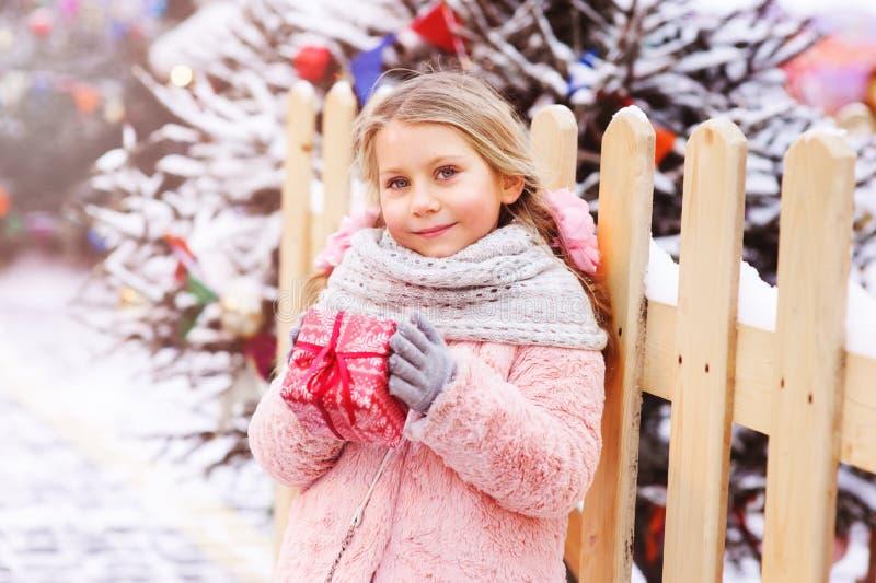 gåva för jul för lycklig barnflicka som hållande är utomhus- på gå i snöig vinterstad arkivbild