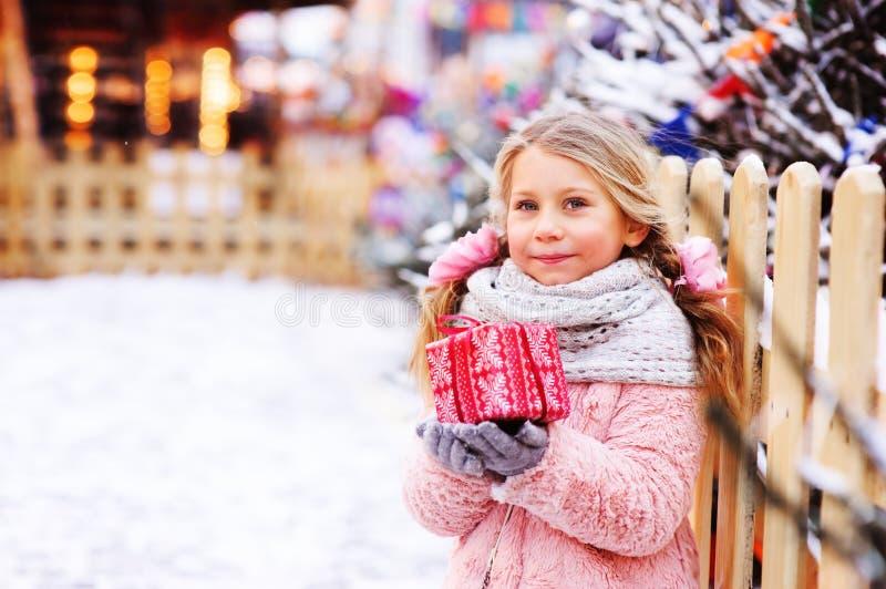 gåva för jul för lycklig barnflicka som hållande är utomhus- på gå i snöig vinterstad royaltyfria foton