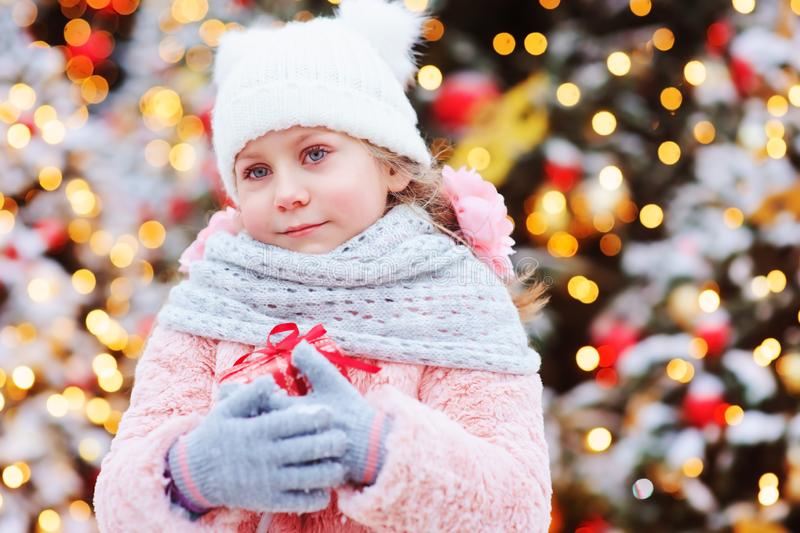 gåva för jul för lycklig barnflicka som hållande är utomhus- på gå i snöig vinterstad arkivbilder