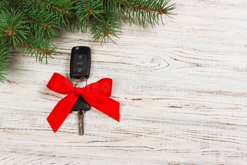 Gåva för julbiltangenter Närbildsikt av biltangenter med den röda pilbågen som gåva på träbakgrund royaltyfria bilder