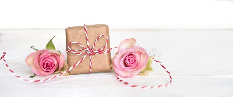 Gåva för moderdag med en ögla och rosa färgrosor arkivbilder