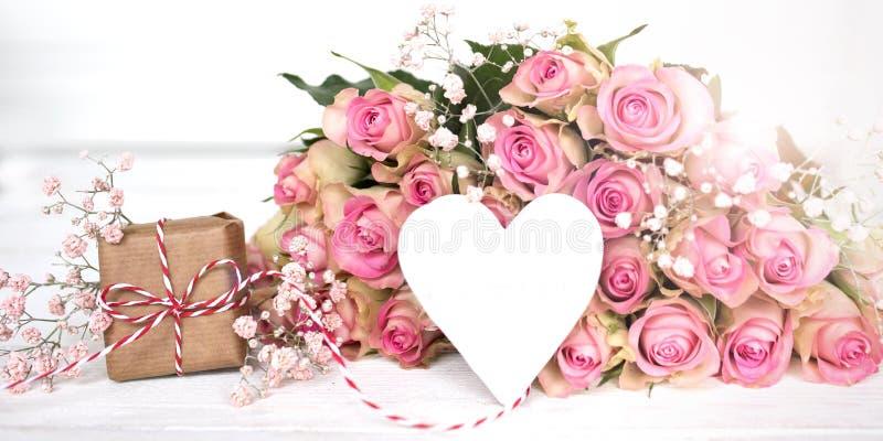 Gåva för moderdag med rosor för en hjärta och rosa färg arkivfoto
