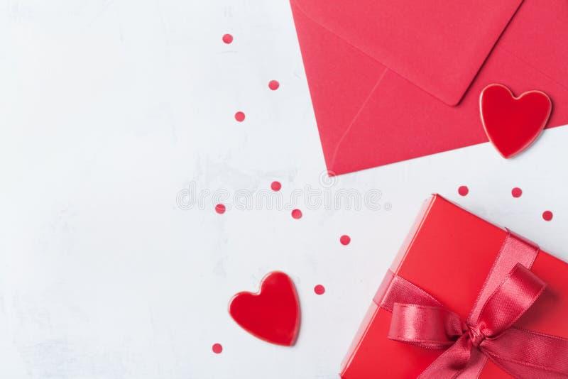 Gåva, kuvert och röd hjärta på den vita tabellen för att hälsa på valentindag Lekmanna- lägenhet royaltyfri fotografi
