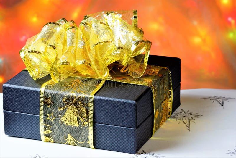Gåva på bakgrunden av ljusa julljus Glatt fira viktiga händelser, ge gåvor och blommor till älskat ditt arkivfoton