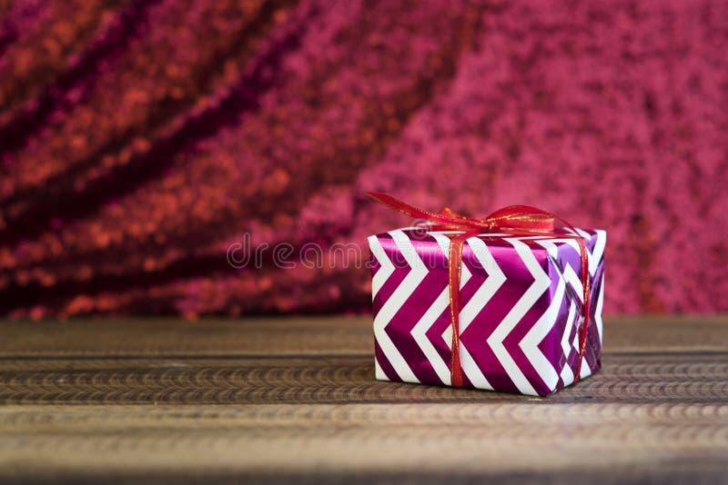 Gåva/gåva på en trätabell med skinande röd bakgrund royaltyfria foton