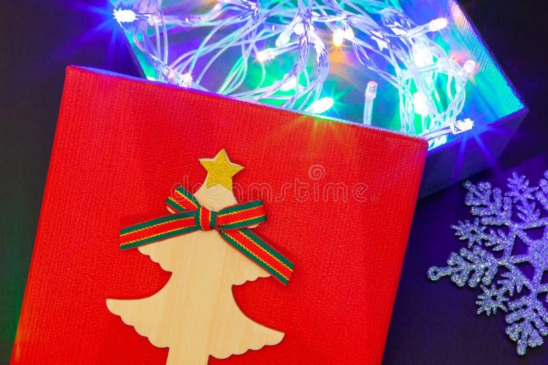 Gåvaask i rött med en girland av ljus för en gåva för det nya året eller födelsedagen Närbild arkivfoton