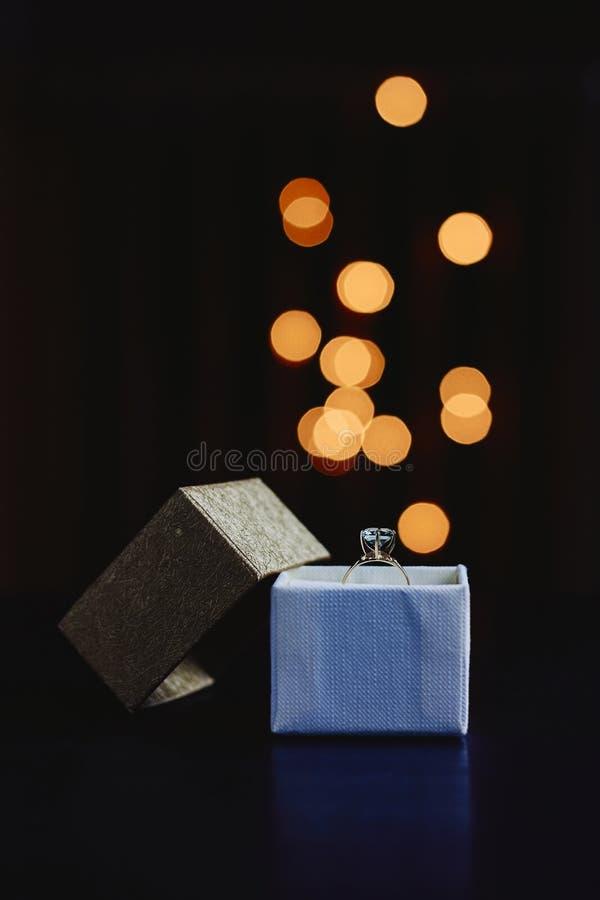 Gåvaask med den guld- cirkeln på mörk bakgrund med bokehljus arkivfoto