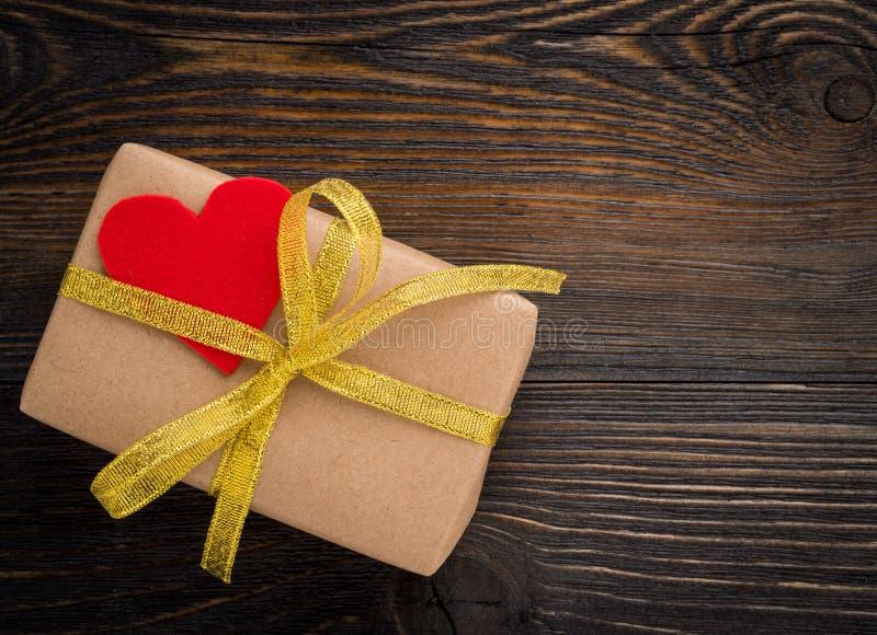 Gåvaask med det guld- bandet och röd hjärta på trätexturmörker royaltyfri foto