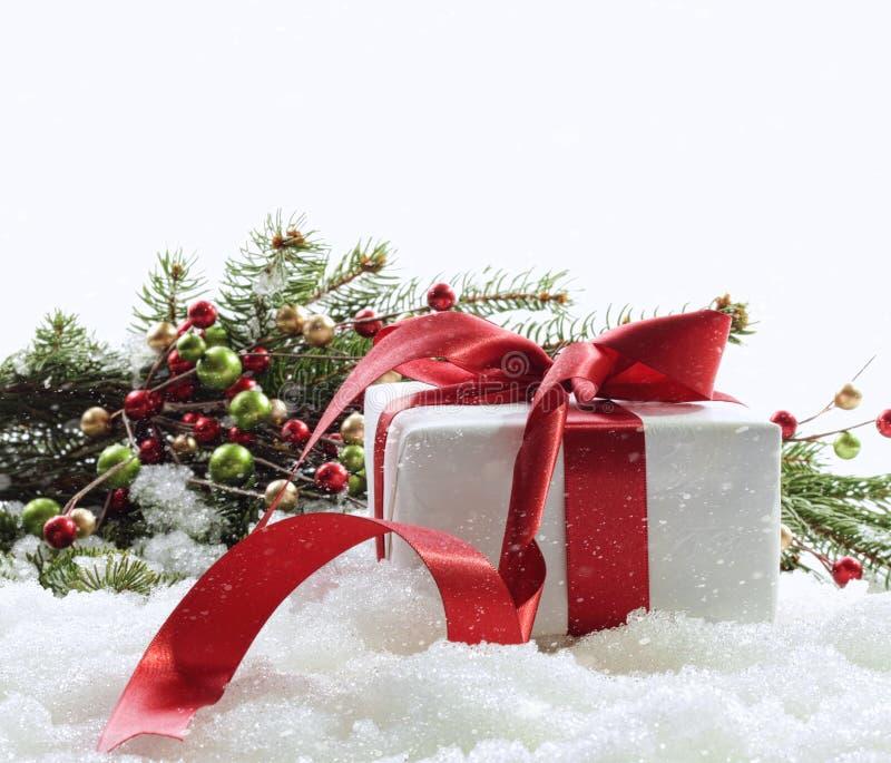 Gåvaask med det röda bandet i snow på white royaltyfri foto