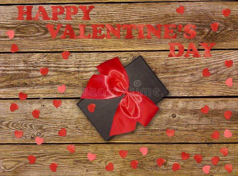 Gåvaask med det röda pilbågebandet och pappershjärta på trätabellen för valentindag arkivfoton