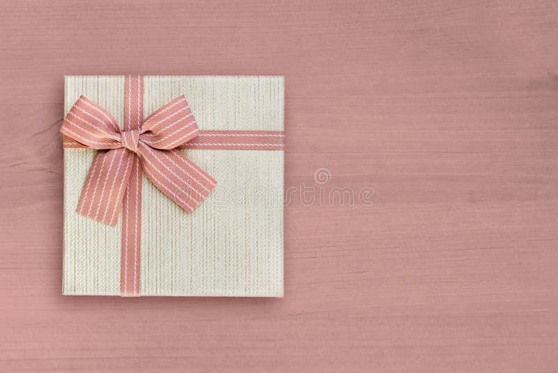 Gåvaask med det rosa bandet på rosa trä, kopieringsutrymme, bästa sikt royaltyfria foton