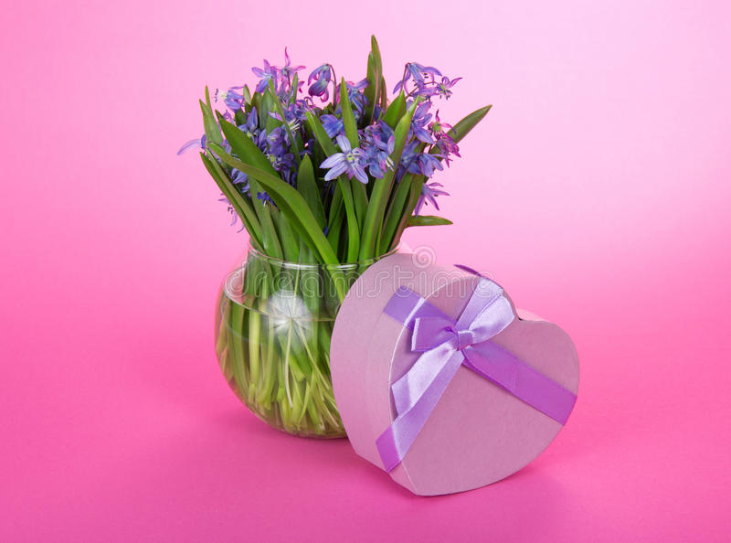 Gåvaask med ett band och blommor i vas royaltyfria foton