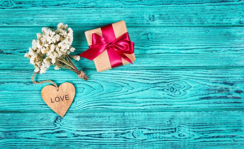 Gåvaask med satängbandet, blommor och hjärta på en blå träbakgrund Celebratory begrepp kopiera avstånd arkivbild