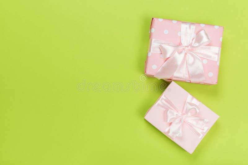 Gåvaask som slås in i pastellfärgat papper med det rosa bandet på grön yttersida fotografering för bildbyråer