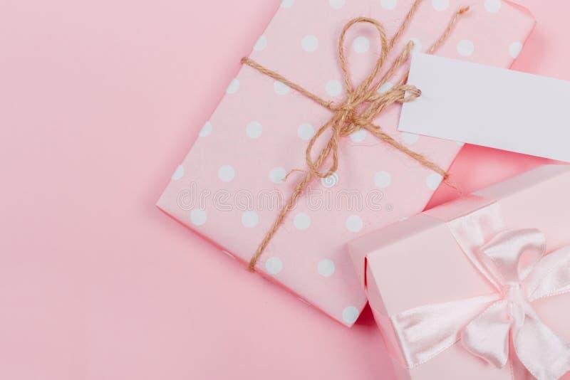 Gåvaask som slås in i pastellfärgat papper med det rosa bandet på rosa yttersida Bästa sikt och med kopieringsutrymme arkivbilder