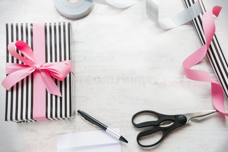 Gåvaask som slås in i svartvitt randigt papper med rosa band- och inpackningsmaterial på en vit wood gammal bakgrund fotografering för bildbyråer