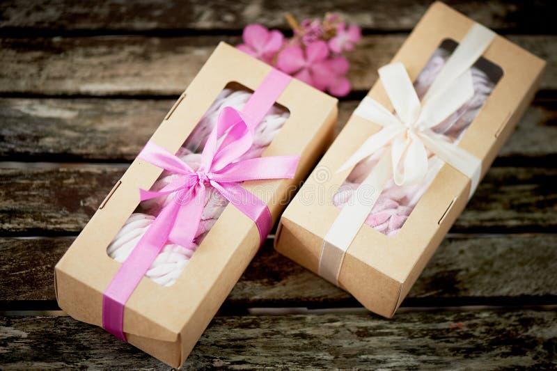 Gåvaaskar av marshmallower från konditor, en komplimang På en träbakgrund roman arkivbilder