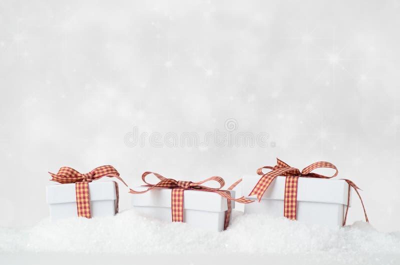 Gåvaaskar för vit jul i snö med Bokeh bakgrund royaltyfria foton