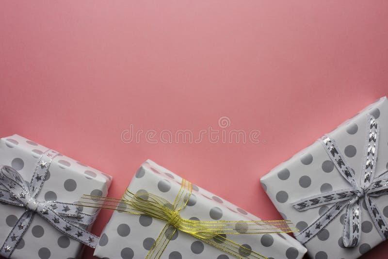 Gåvaaskar i ärtor med silver och guld- pilbågar på rosa bakgrund arkivfoto