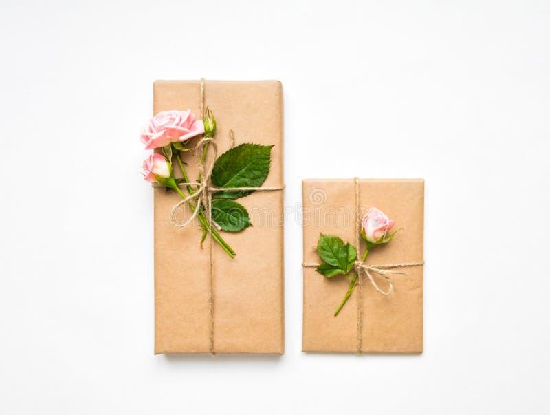 Gåvaaskar i eco skyler över brister på vit bakgrund Gåvor som dekoreras med rosor Semestra begreppet, den bästa sikten, den lekma arkivbilder