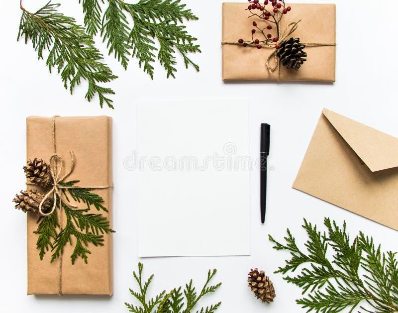 Gåvaaskar i ecopapper och en bokstav på vit bakgrund Jul eller annan feriebegrepp, bästa sikt, lekmanna- lägenhet arkivfoto