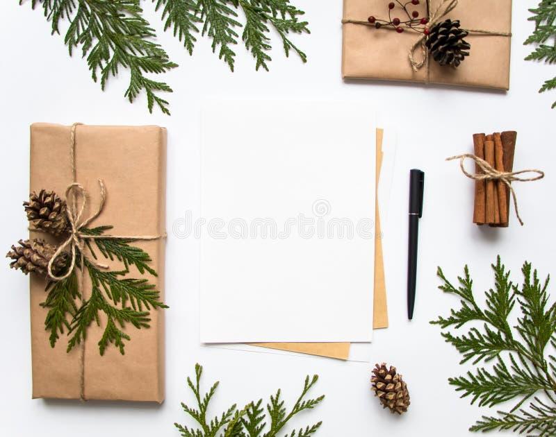 Gåvaaskar i hantverkpapper och en bokstav på vit bakgrund Jul eller annan feriebegrepp, bästa sikt, lekmanna- lägenhet royaltyfri fotografi