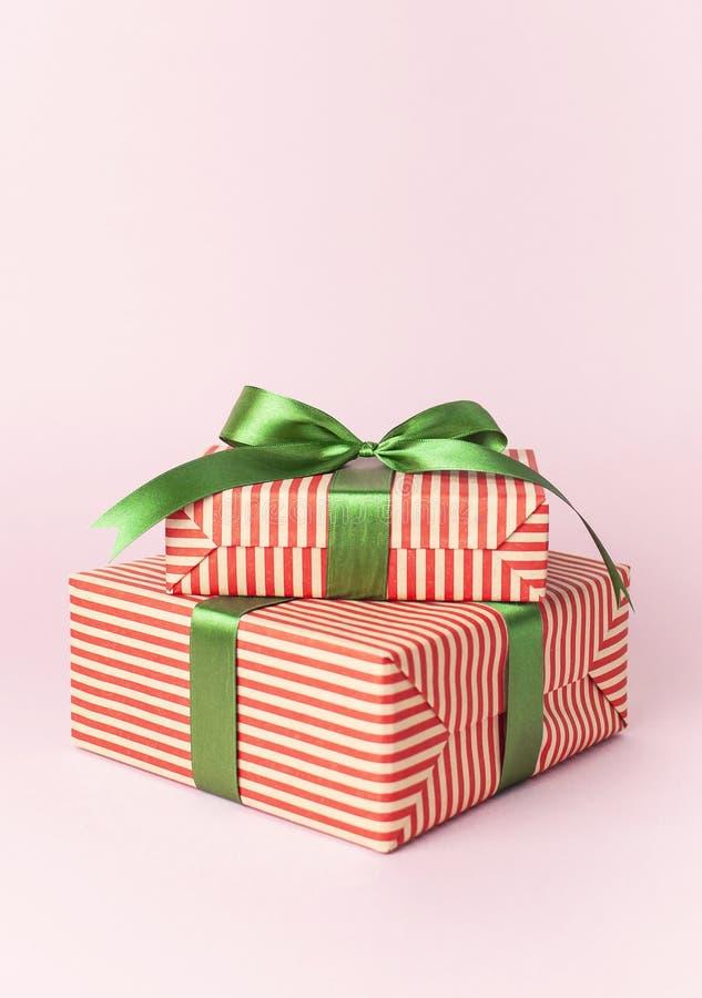 Gåvaaskar med det gröna bandet på rosa bakgrundslägenhet lägger Semestra begreppet, det nya året eller julgåvaasken, gåvaXmas-fer royaltyfri bild