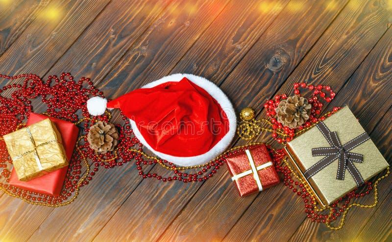 Gåvaaskar med pärlor, leksaker och den Santa Claus hatten arkivfoton