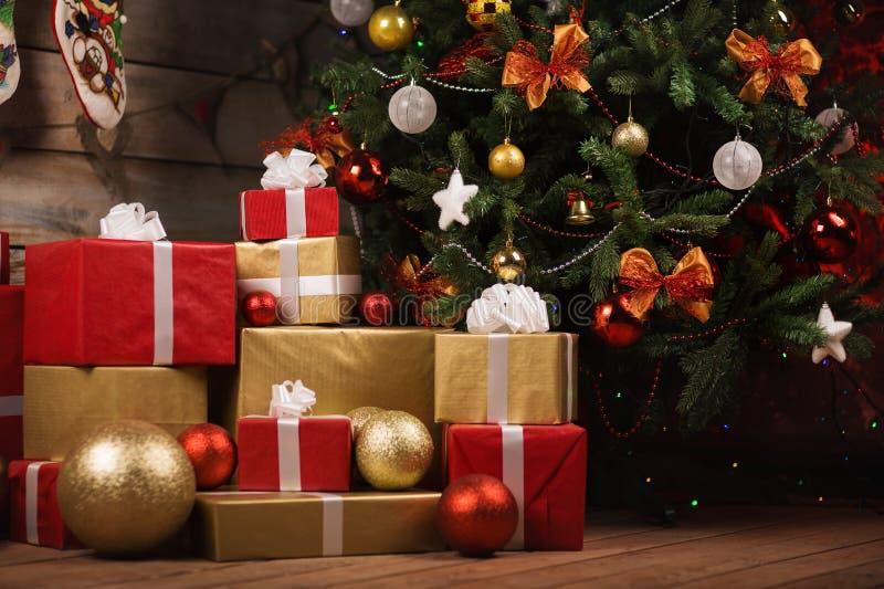 Gåvaaskar och bollar under julträd arkivfoto