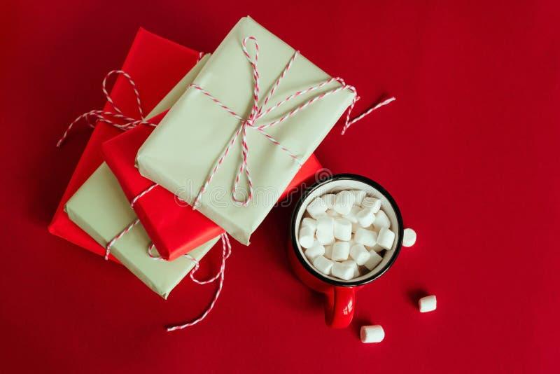 gåvaaskar och kopp med marshmallower på röd bakgrund royaltyfri bild