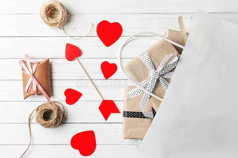 Gåvaaskar, papperssnitthjärta och shoppingpåse på en vit träbakgrund Garneringar för dag för valentin` s royaltyfri foto